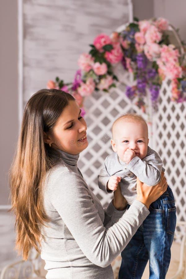 Potomstwa matkują kobiety przytulenia w ona i mienia ręki dziecka dziecka dzieciaka chłopiec smilling śmiać się zdjęcia stock