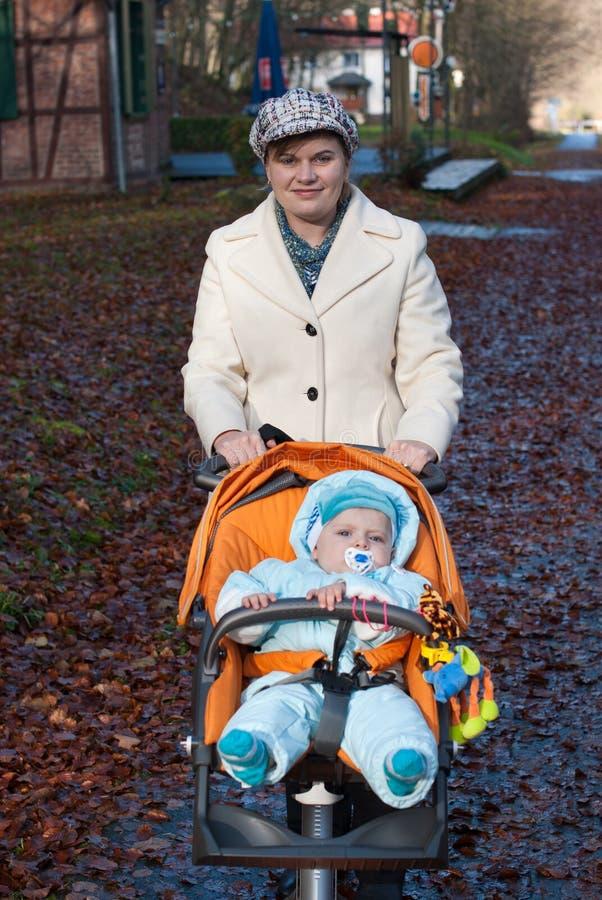 Potomstwa matkują odprowadzenie z chłopiec w pomarańczowym pram obrazy stock