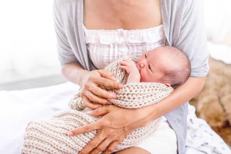 Potomstwa matkują opakowanie jej mała dziewczynka z beżowym pulowerem zdjęcia royalty free