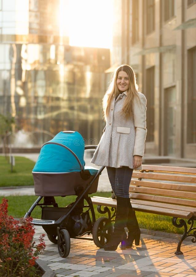 Potomstwa matkują pozować z wózkiem spacerowym przy słonecznym dniem zdjęcie royalty free