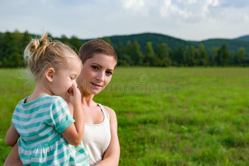 Potomstwa matkują przewożenia preschool córki w jej rękach podczas spaceru przez łąki zdjęcie royalty free