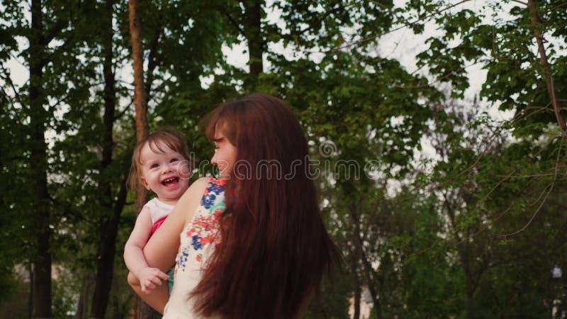 Potomstwa matkują sztuki w parku z małym dzieckiem śmia się je w ona i trząść ręki obraz stock