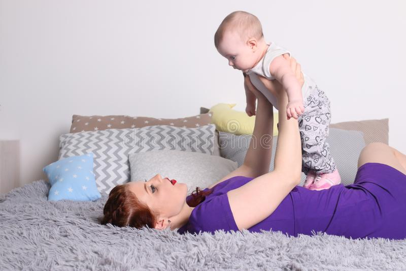 Potomstwa matkują sztuki z jej małym dzieckiem na łóżku obrazy royalty free