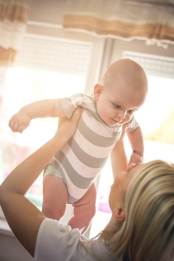 Potomstwa matkują trzymać jej małej chłopiec wysoka w ręce obrazy stock