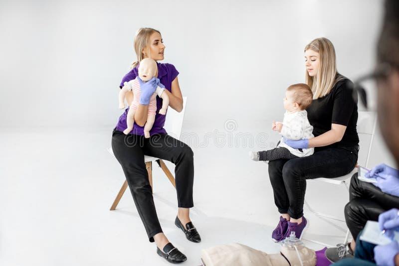 Potomstwa matkują z dzieckiem podczas pierwszej pomocy szkolenia obrazy royalty free