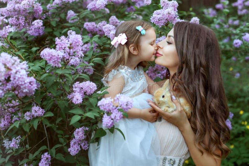Potomstwa matkują z jej córką blisko lilego krzaka fotografia stock