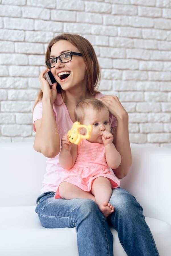 Potomstwa matkują z małym dzieckiem używa smartphone obrazy stock