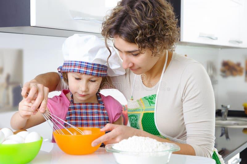 Potomstwa matkują z małymi córki narządzania ciastkami zdjęcia royalty free