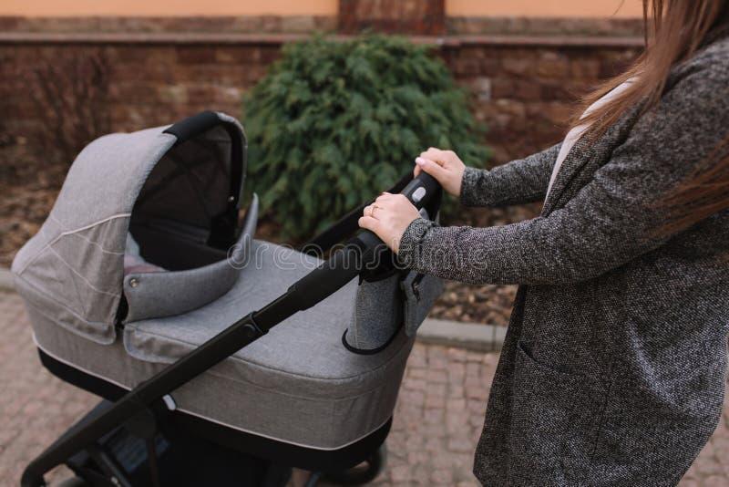 Potomstwa matkuj? odprowadzenie z jej nowonarodzonym dzieckiem w spacerowiczu Popielaty pram Pi?kna mama w okularach przeciws?one zdjęcia royalty free