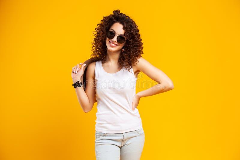 Potomstwa modelują wyrażać emocje podczas gdy pozujący na salowym photoshoot Elegancka kędzierzawa kobieta ma zabawę w żółtym stu fotografia stock