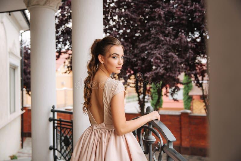 Potomstwa modelują z wielką wieczór suknią stoją bezczynnie restaurację Brunetki dziewczyna pięknego włosianego styl i makeup obraz royalty free