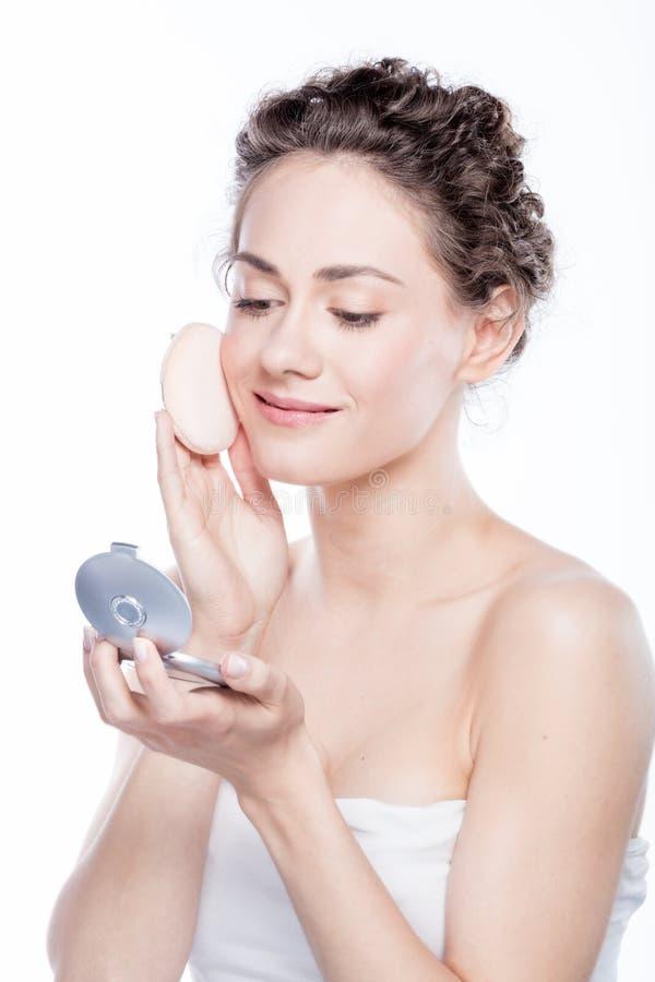 Potomstwa, naturalny kobiety kładzenia proszek na jej twarzy zdjęcie stock