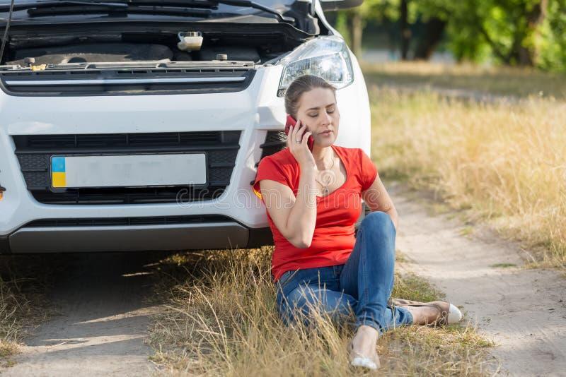 Potomstwa niepokoją kobieta płacz przez łamanej samochodowej dzwoni samochód usługa dla pomocy obrazy stock