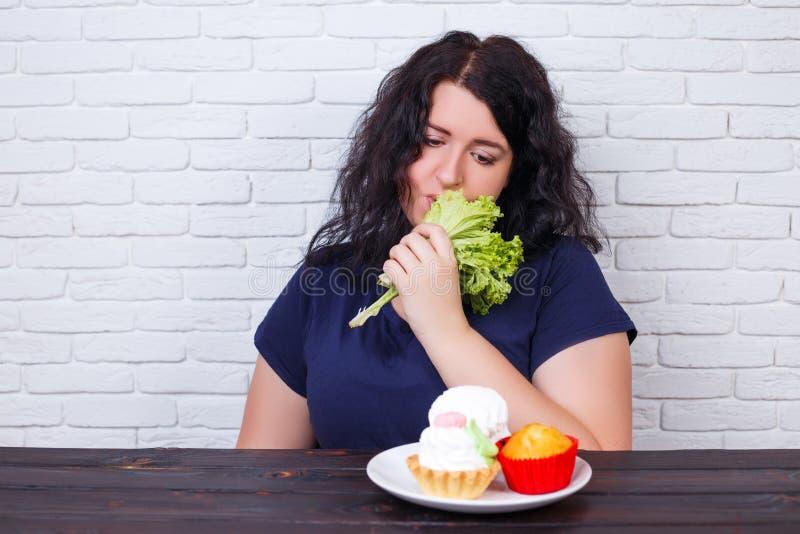 Potomstwa niepokoją z nadwagą kobiety zanudzającej diety je zdrowego jedzenie fotografia stock