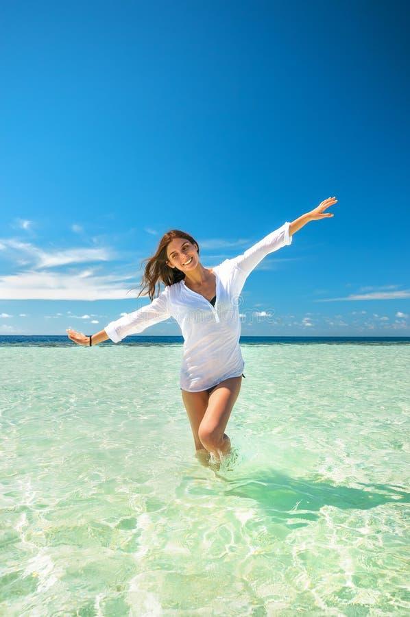 Potomstwa odchudzają kobiety bawić się w czystej wodzie morskiej robi samolotowym skrzydłom pod głębokim niebieskim niebem Wakacj zdjęcia stock