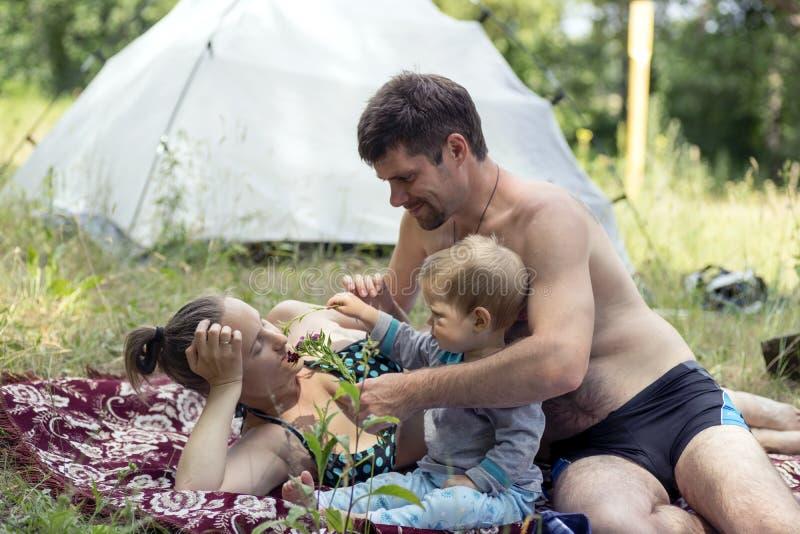 Potomstwa ojcowie, matka 1 i syn, 3 roku kłama na trawie pinkin Mąż daje żona kwiaty zdjęcia stock