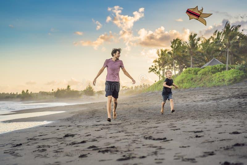 Potomstwa ojcują i jego syna bieg z kanią na plaży zdjęcie stock
