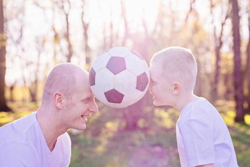 Potomstwa ojcują i syn bawić się z piłką na zielonej trawie w parku zdjęcia royalty free