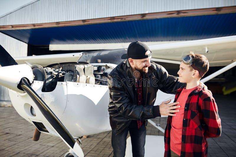 Potomstwa ojcują stojaki z jego synem przed małym śmigłowym samolotem zdjęcia royalty free