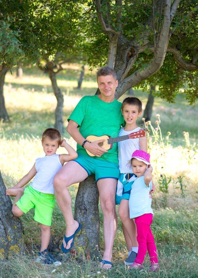 Potomstwa ojcują sztuki gitara dla jego młodych dzieci w lesie obraz stock