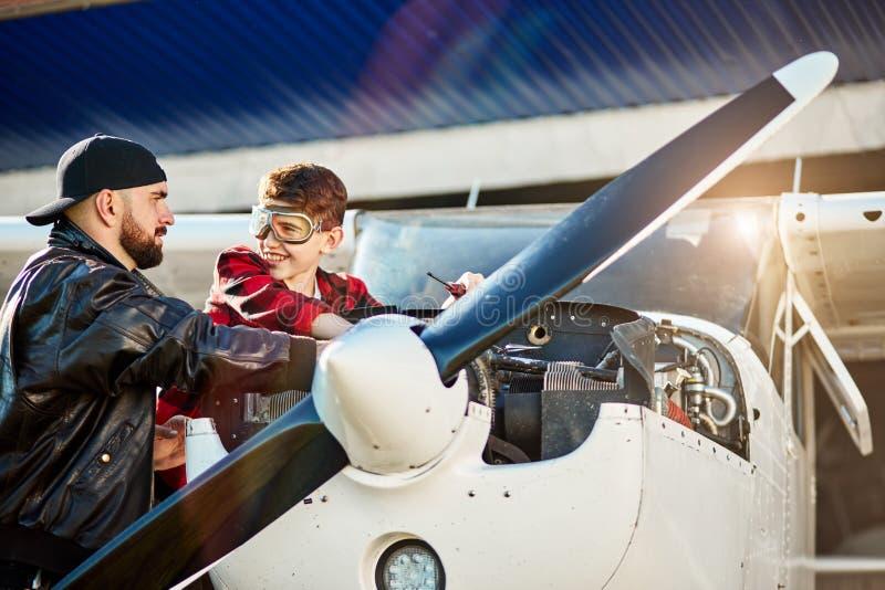Potomstwa ojcują turbinę lekki śmigłowy samolot i sprawdzają silnika przed lotem i fotografia stock