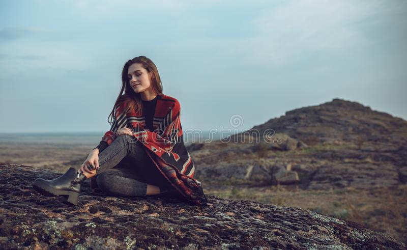 Potomstwa, piękny dziewczyny obsiadanie na ziemi przeciw tłu teren górzysty Szkocka krata drapująca nad girl's zdjęcie stock