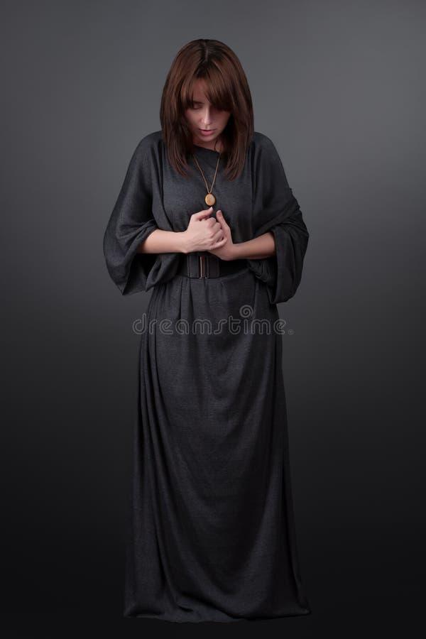 potomstwa portreta modlenia kobiety potomstwa Modlitewna dziewczyna ubierał w Vestments magdalenka na szarym pracownianym tle zdjęcia stock