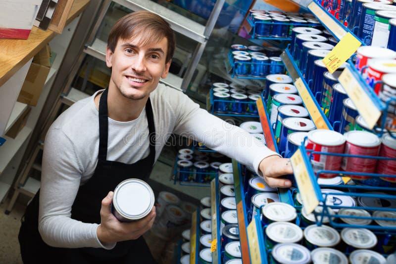 Potomstwa robią zakupy pracownika pozuje blisko stojaka z farbą zdjęcia stock