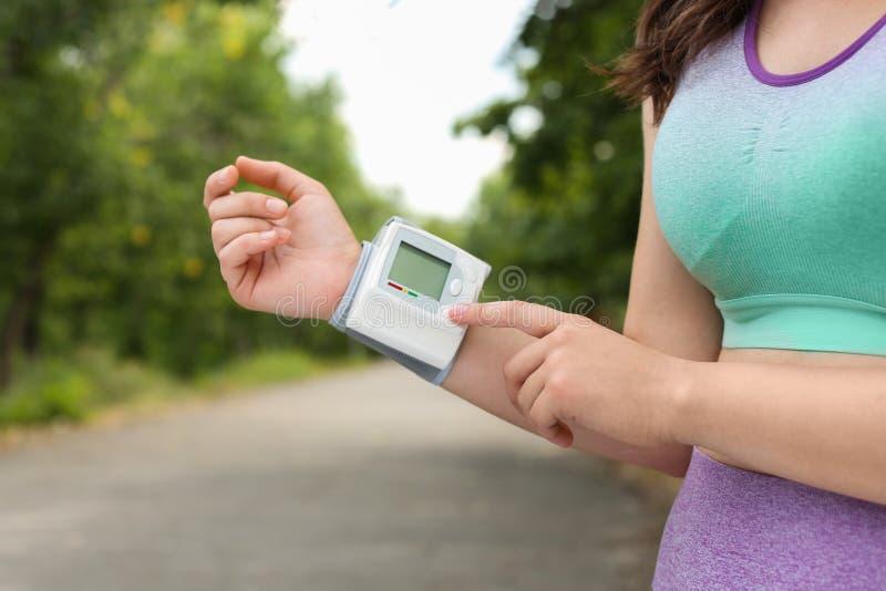 Potomstwa sprawdza puls z urządzeniem medycznym po tym jak trenujący w parku, zbliżenie obraz royalty free