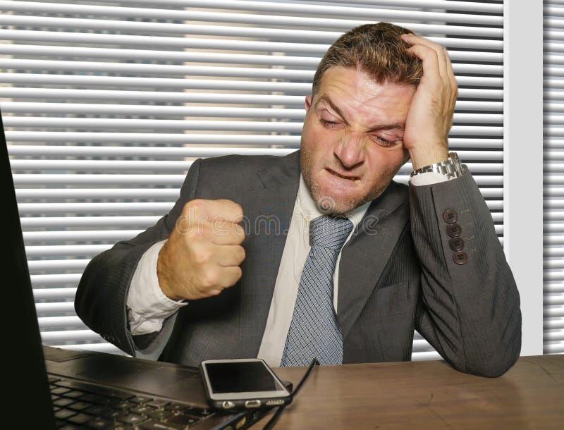 Potomstwa stresujący się i przytłaczający biznesmen w uderza pięścią telefonu komórkowego działanie przy biurowym laptopem kostiu obraz stock