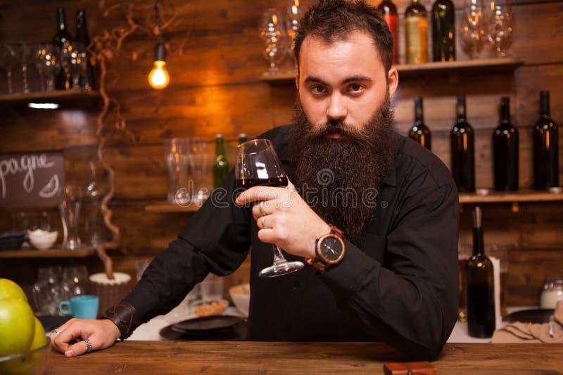 Potomstwa tatuowali barmanu kosztuje szkło wino z wielką brodą fotografia royalty free