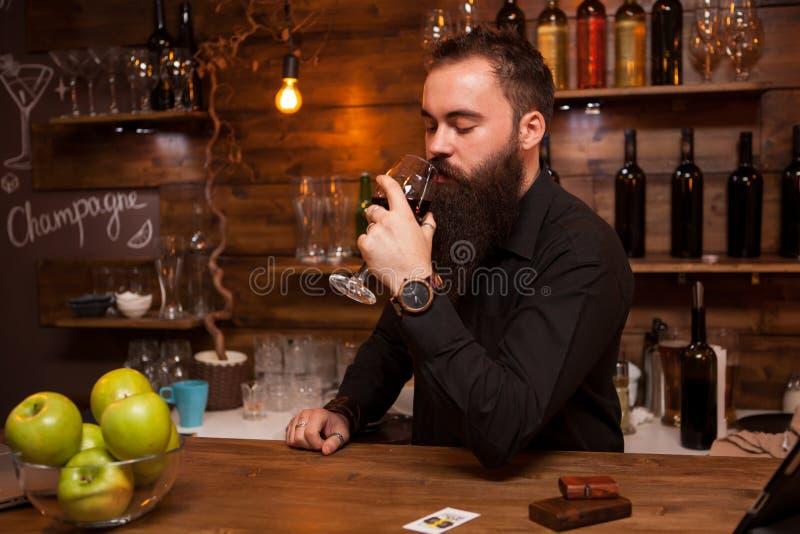Potomstwa tatuowali barmanu kosztuje szkło wino z wielką brodą obraz stock
