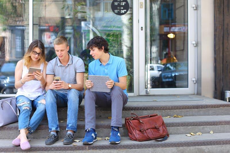 Potomstwa trzy przyjaciela siedzi podłoga w ulicie, opowiadający, używać fotografia royalty free