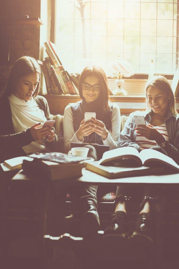 Potomstwa trzy uczeń dziewczyny przy kawiarnią używać mądrze telefon obrazy royalty free