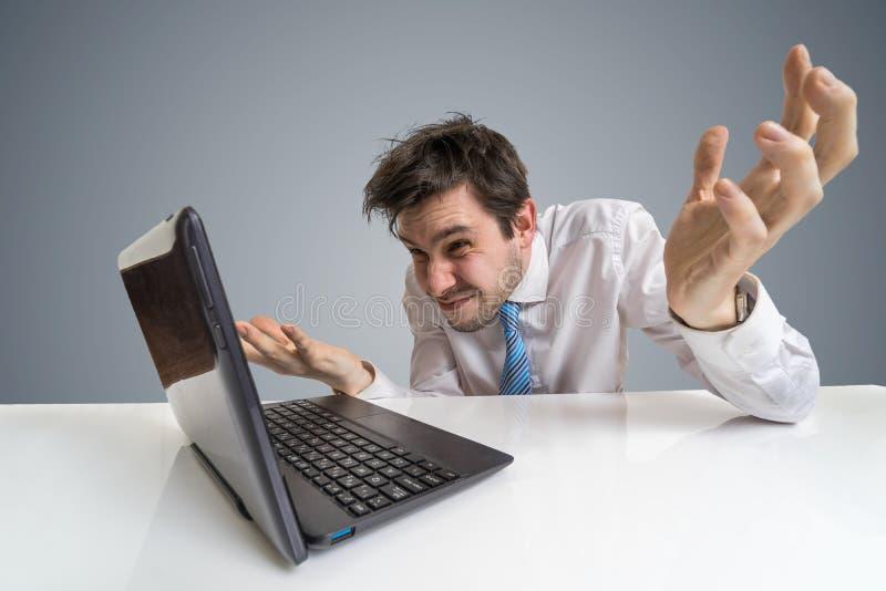 Potomstwa wprawiać w zakłopotanie i niepewny mężczyzna pracują z laptopem fotografia stock