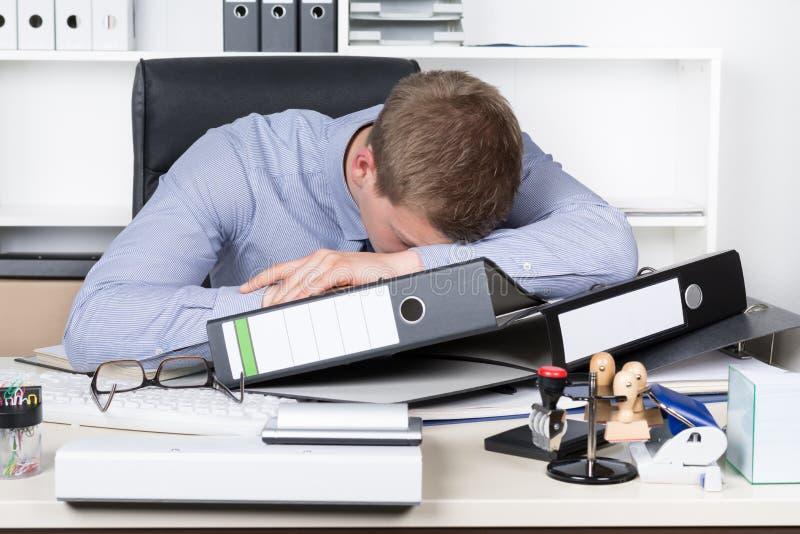 Potomstwa wyczerpujący obsługują kłamają na biurku w biurze zdjęcia stock