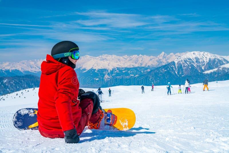 Potomstwa z snowboard mężczyzna obsiadaniem na wierzchołku góra fotografia royalty free