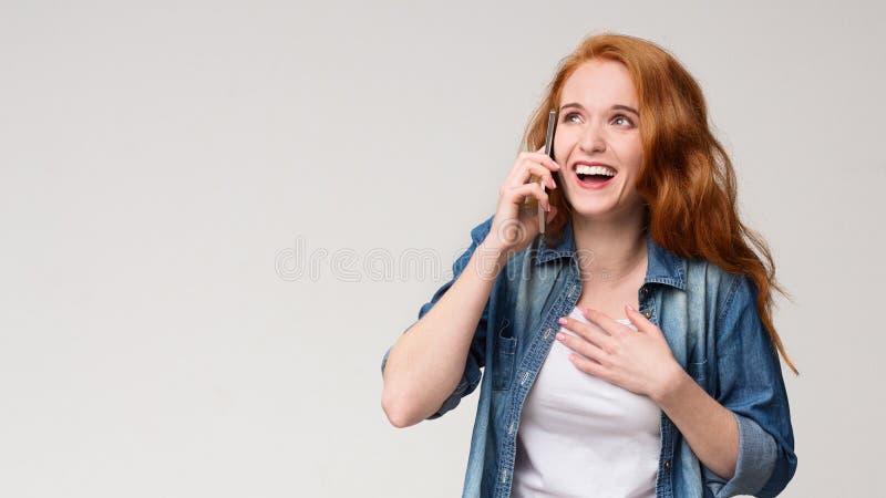 Potomstwa zadziwiali rudzielec kobiety opowiada na telefonie, fotografia stock