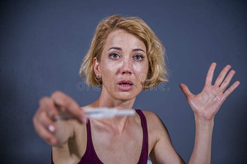 Potomstwa zaskakiwali kobieta w ciąży mienia pozytywnego wynika ciążowego test, szokowali i stresu i niewiary w unwan w twarzy wy fotografia royalty free