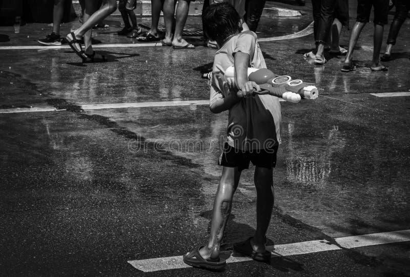 Potomstwo chłopiec strzały z wodą w Songkran obraz stock