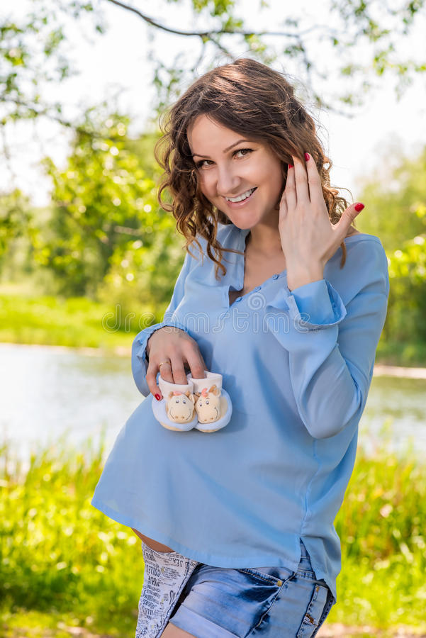 Potomstwo ciężarna dziewczyna w bielu sarafan na szkockiej kracie w parku fotografia stock