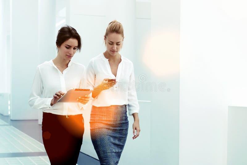 Potomstwo doświadczający bizneswomany pastylki i komórki drużynowy używa cyfrowy telefon podczas gdy spacer wpólnie sala konferen zdjęcie royalty free