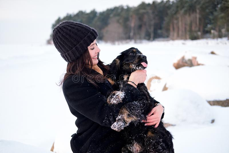 Potomstwo dosyć caucasian kobieta trzyma jej psa na rękach, bawić się, śmia się outdoors w parku zdjęcie stock