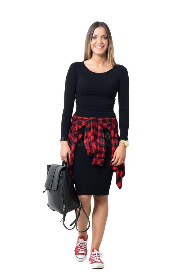 Potomstwo dosyć przypadkowa kobieta w czerni sukni przewożenia torby odprowadzeniu w kierunku kamery ono uśmiecha się obraz royalty free