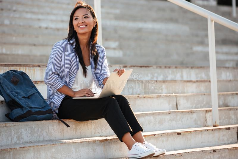 Potomstwo dosyć rozochocony azjatykci uczeń, trzyma laptop, podczas gdy sitti fotografia royalty free