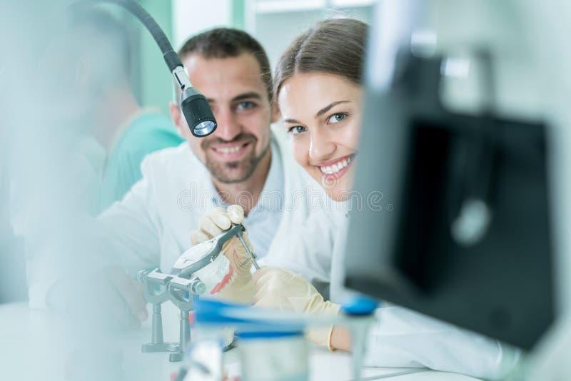 Potomstwo drużyna stomatologiczni technicy robi zębu prostetics Proces obrazy stock