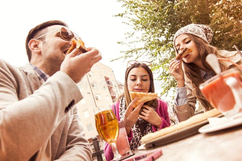 Potomstwo grupa roześmiani ludzie je pizzę i ma zabawę zdjęcie stock