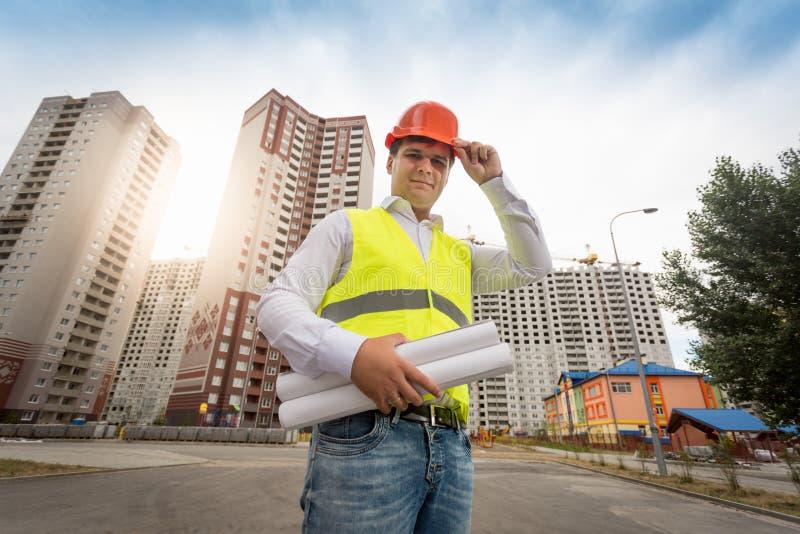 Potomstwo inżyniera pozycja przy nowymi budynkami z projektami obrazy stock