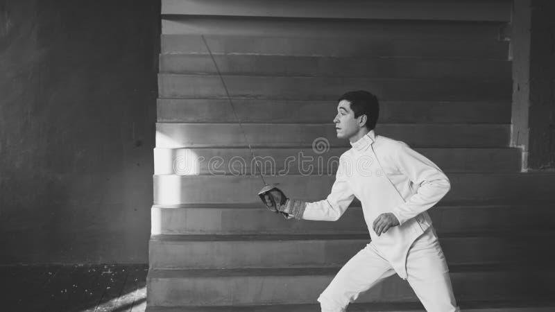 Potomstwo koncentrujący szermierza mężczyzna praktyki fechtunek ćwiczy i trenujący dla olimpiad turniejowych w studiu indoors zdjęcie stock