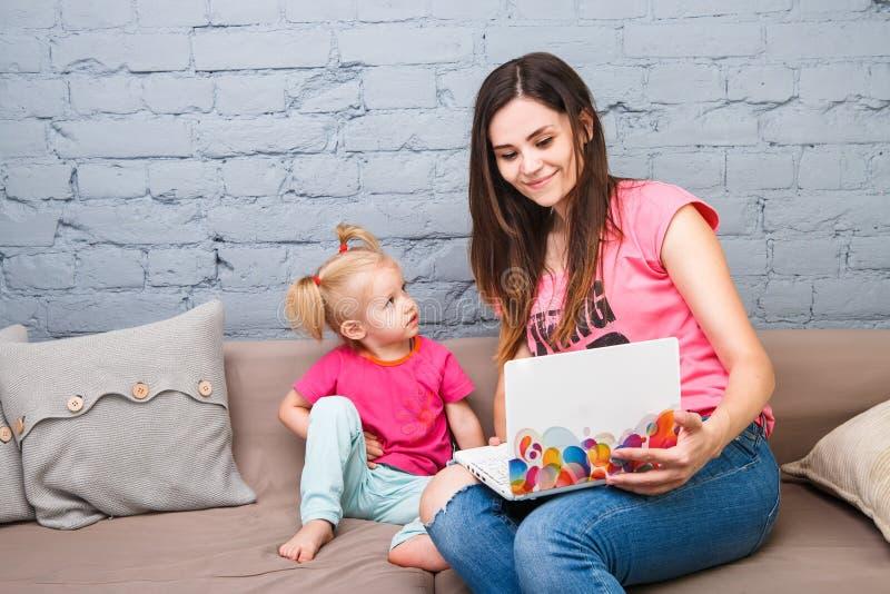 Potomstwo matka i dwa roczniaka dziewczyna z blondynu obsiadaniem na używać laptopie i leżance Ubierają w jaskrawych menchii ubra zdjęcie royalty free